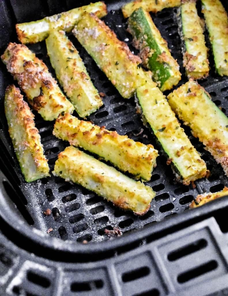 air fryer basket filled with cooked zucchini fries