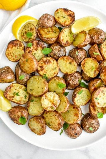 crispy air fryer Greek potatoes on a platter with lemon wedges