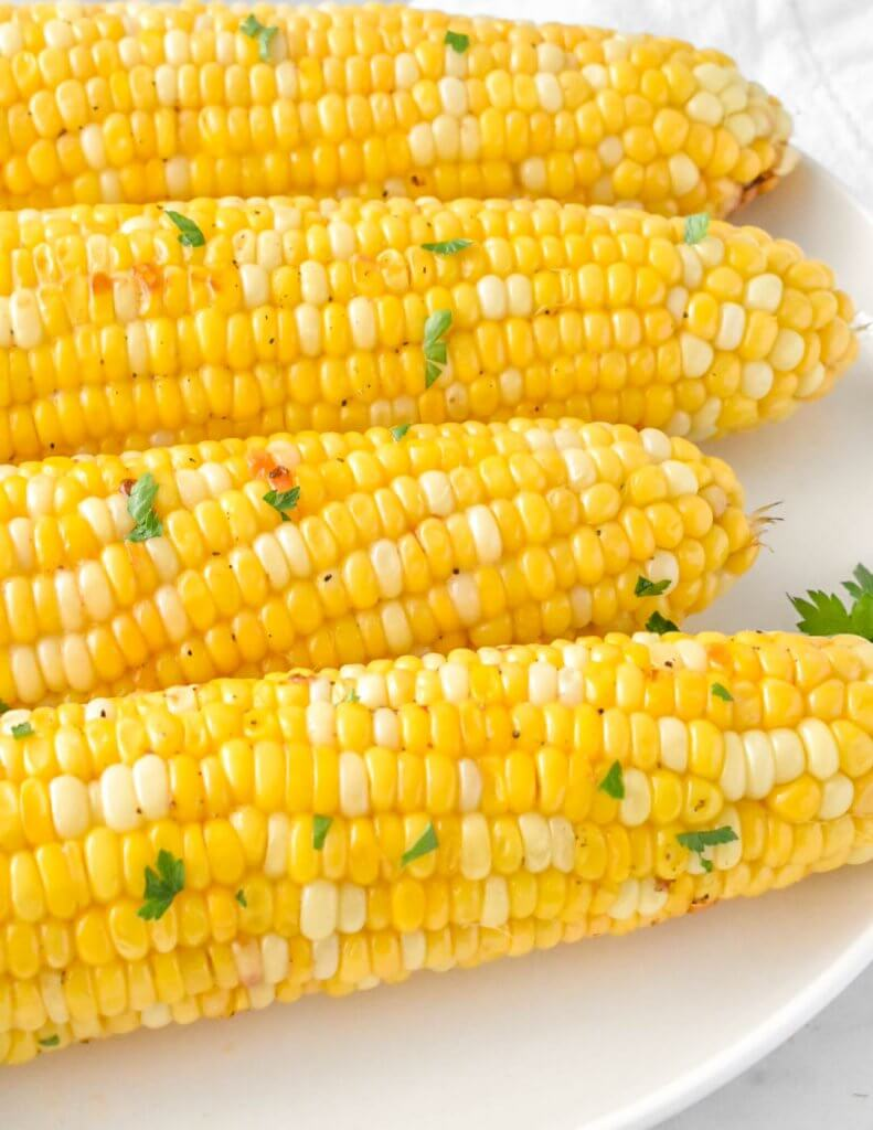 roasted corn on the cob on a white platter