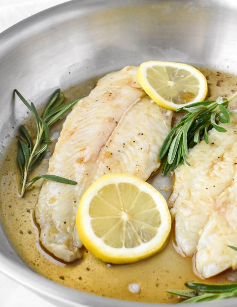 basa fillet topped with lemon slices in a pan with rosemary sprigs