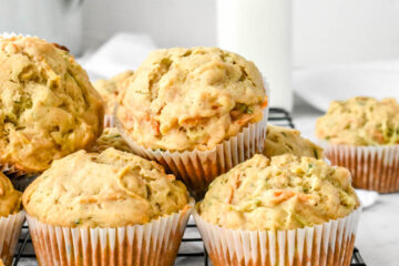 pile of carrot zucchini muffins on a cooling rack