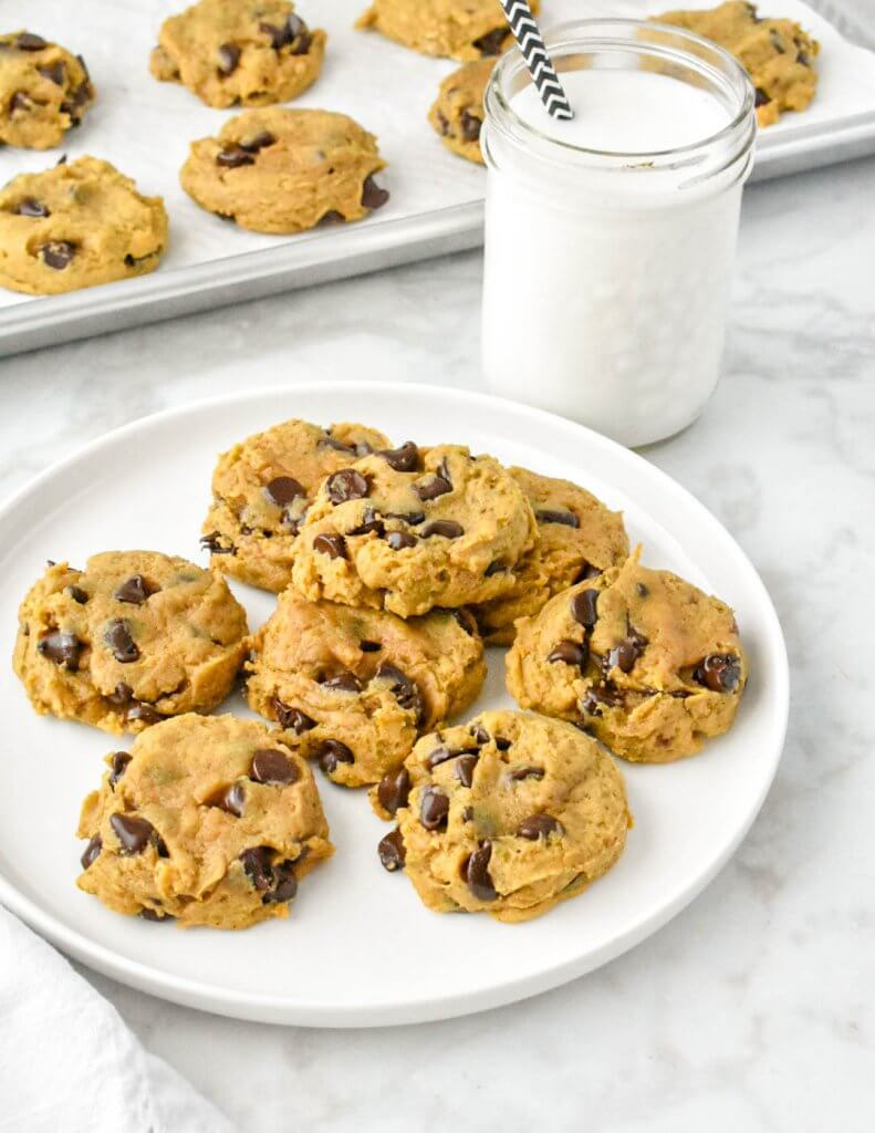 a plate of pumpkin chocolate chip cookies and a glass of milk