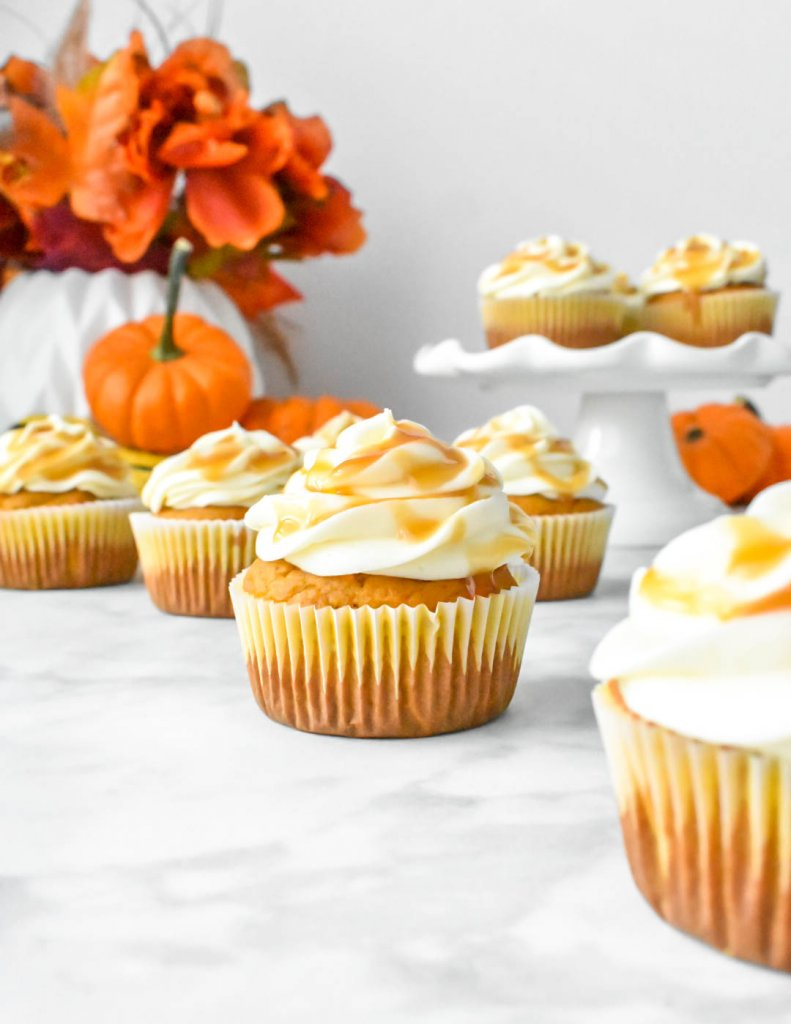 Pumpkin Cupcakes with Cream Cheese Frosting on a Fall table